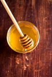 Aromatic honey with wooden honey dipper in a jar on a wooden table, selective focus, closeup. Healthy and organic food option. Ima. Ge with copy space stock images