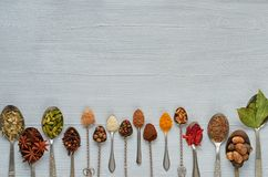 Aromatic Indian spices and herbs on metal spoons: star anise, fragrant pepper, cinnamon, nutmeg, bay leaves, paprika, clove. Spices texture background royalty free stock images