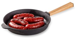 Aromatic meat fried sausages in cast-iron frying pan with wooden. Aromatic meat fried sausages in a cast-iron frying pan with wooden handle .Isolated on white Stock Image