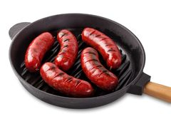 Aromatic meat sausages fried in cast-iron frying pan with handle. Aromatic meat sausages fried in a cast-iron frying pan with handle. Isolated on white Royalty Free Stock Photography
