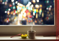 Aromatic mug with coffee and cupcakes is on the window sill at the window in the evening time.Soft and blur conception. Stock Photos