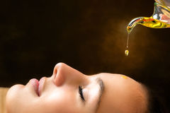 Aromatic oil dripping on female face. Macro close up portrait of young woman at ayurvedic massage session with aromatic oil dripping on face Royalty Free Stock Photos