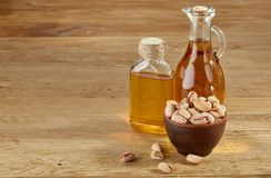 Aromatic oil in a glass jar and bottle with pistachios in bowl on wooden table, close-up. Composition of aromatic oil in a glass jar and bottle with unpeeled Stock Photo