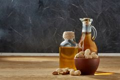 Aromatic Oil In A Glass Jar And Bottle With Peanuts In Bowl On Wooden Table, Close-up. Royalty Free Stock Images