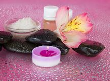 Aromatic oil, salt, candle, stones and flower Royalty Free Stock Images