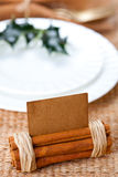 Aromatic place card with holly twig in white plate Royalty Free Stock Images