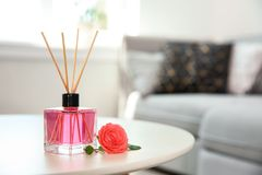Aromatic reed air freshener and rose on table. Indoors stock photography