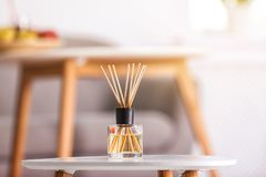 Aromatic reed air freshener on table. Against blurred background royalty free stock photo
