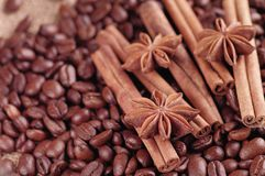 Aromatic roasted coffee beans and anis or badian, sticks of natural cinnamon on background close up.  royalty free stock photos