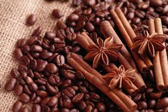 Aromatic roasted coffee beans and anis or badian, sticks of natural cinnamon on background close up.  royalty free stock image