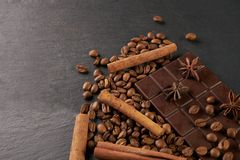 Aromatic set of chocolate bar, arabica coffee beans,. Anise and cinnamon on dark stone background with copy space Stock Image