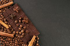 Aromatic set of chocolate bar, arabica coffee beans. Anise and cinnamon on dark stone background with copy space Stock Photography
