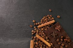 Aromatic set of chocolate bar, arabica coffee beans. Anise and cinnamon on dark stone background with copy space Royalty Free Stock Photography