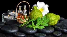 Aromatic spa of bottles essential oil in basket, fresh mint, rosemary, bergamot fruits, flower and candles on black zen stones stock photo