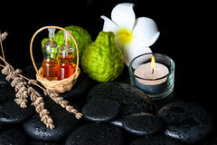 Aromatic spa concept of bottles essential oil, bergamot fruits. Plumeria flower, candle and dried lavenders on zen stones stock photo