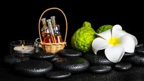 Aromatic spa setting of bergamot fruits, candles, plumeria flowe Royalty Free Stock Photo