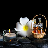 Aromatic spa setting of plumeria flower, candles and bottles ess Royalty Free Stock Image