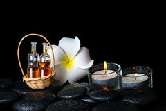 Aromatic spa setting of plumeria flower, candles and bottles ess Royalty Free Stock Photo