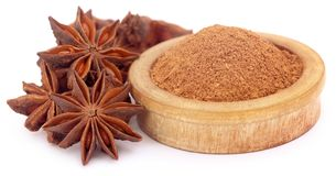 Aromatic star anise. With powdered spice over white background Royalty Free Stock Photography