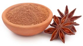 Aromatic star anise. With powdered spice over white background Royalty Free Stock Image