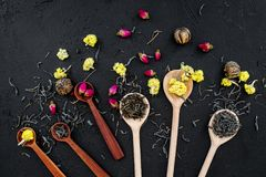 Aromatic tea. Wooden spoons with dried tea leaves, flowers and spices on black background top view Royalty Free Stock Photo