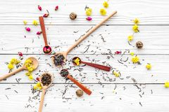 Aromatic tea. Wooden spoons with dried tea leaves, flowers and spices on white wooden background top view Royalty Free Stock Images