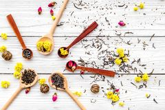 Aromatic tea. Wooden spoons with dried tea leaves, flowers and spices on white wooden background top view Stock Photography