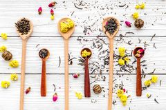 Aromatic tea. Wooden spoons with dried tea leaves, flowers and spices on white wooden background top view Stock Photos