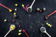 Aromatic tea. Wooden spoons with dried tea leaves, flowers and spices on black background top view copyspace Royalty Free Stock Image