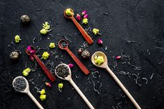 Aromatic tea. Wooden spoons with dried tea leaves, flowers and spices on black background top view copyspace Stock Photo