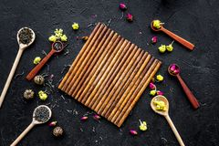 Aromatic tea. Wooden spoons with dried tea leaves, flowers and spices on black background top view mockup Stock Images