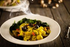 Aromatic vegan pasta with mushrooms without eggs. Pasta from vegan dough. Don`t contain eggs and milk. All ingredients are vegan. Tasty pasta bowl with spinach Royalty Free Stock Photo