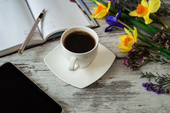 Aromatic work morning with cup of black coffee. Aromatic work morning with cup of black coffee, tablet and notes. Beautiful yellow daffodils, lilac irises and Stock Image