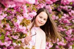 Aromatisch bloesemconcept Meisjestoerist het stellen dichtbij sakura Tedere bloei Kind op roze bloemen van de achtergrond van de  royalty-vrije stock afbeelding
