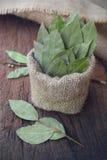aromatisch droog laurierblad in jute en laurierblad op houten raad Droog kruid royalty-vrije stock fotografie