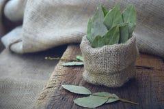 aromatisch droog laurierblad in jute en laurierblad op houten raad Droog kruid royalty-vrije stock afbeeldingen