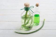 Aromatische Öle in den Glasflaschen mit Scharlachrot auf einer weißen Tabelle Frauenfuß im Wasser Gesunder Lebensstil stockfoto