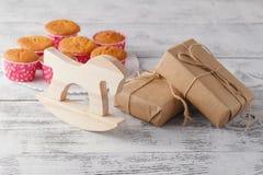 Aromatische Eigengemaakte Citroenmuffins met stuk speelgoed paard en giftbox op Th Stock Afbeelding