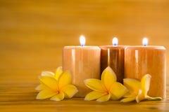 Aromatische Kerzen mit Frangipani auf Bambusmatte Lizenzfreie Stockfotografie