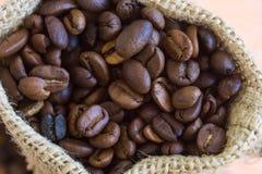 Aromatische koffiebonen in zak Stock Afbeeldingen