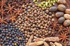 Aromatische kruiden op een donkere bruine plaat - speel anijsplant, geurige peper, calamus wortel, kaneel, notemuskaat, jeneverbe royalty-vrije stock afbeelding