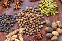 Aromatische kruiden op een donkere plaat - speel anijsplant, geurige peper, calamus wortel, kaneel, notemuskaat, jeneverbessen me royalty-vrije stock fotografie