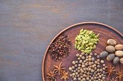 Aromatische kruiden op een donkere plaat - speel anijsplant, geurige peper, calamus wortel, kaneel, notemuskaat op bruine achterg stock afbeeldingen