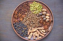 Aromatische kruiden op een donkere plaat - speel anijsplant, geurige peper, calamus wortel, kaneel, notemuskaat op bruine achterg royalty-vrije stock fotografie