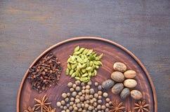 Aromatische kruiden op een donkere plaat - speel anijsplant, geurige peper, calamus wortel, kaneel, notemuskaat op donkere achter royalty-vrije stock afbeeldingen