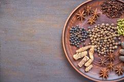 Aromatische kruiden op een donkere plaat - speel anijsplant, geurige peper, calamus wortel, kaneel, notemuskaat op donkere bruine royalty-vrije stock fotografie