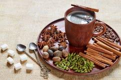 Aromatische masalathee met diverse kruiden op de bruine plaat: kaneel, notemuskaat, kardemom, anijsplantsterren Aromatische koffi stock foto's