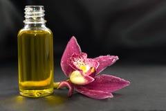 Aromatische massageolie en orchideebloem op donkere achtergrond Stock Foto's
