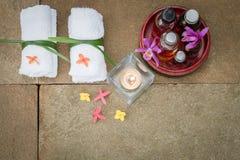 Aromatische olie in grunge houten kom, gebrande kaars, roze geeloranje bloemen, witte handdoek op de uitstekende achtergrond van  royalty-vrije stock afbeelding
