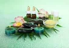 Aromatische olie, zout, kaarsen, stenen en bloem Stock Foto